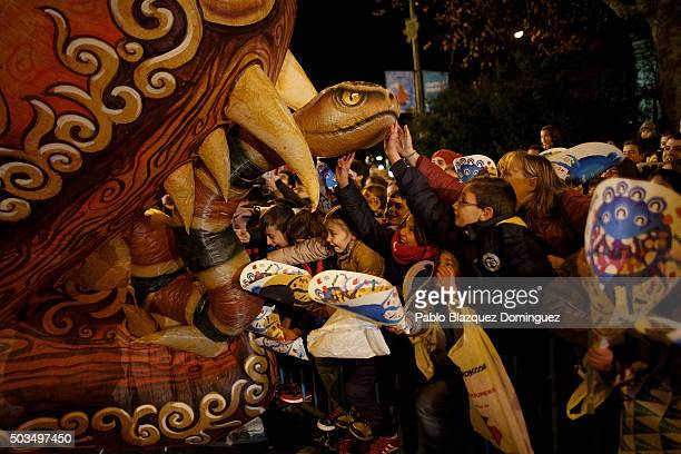 Children touch a balloon depicting a dragon during the 'Cabalgata de Reyes' or the Three Kings parade on January 5 2016 in Madrid Spain The...