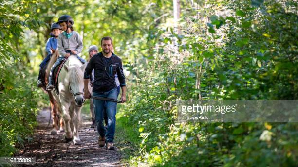 bambini che si allenano a cavallo - andare a cavallo foto e immagini stock