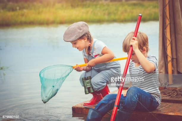 Children traveling on raft and fishing