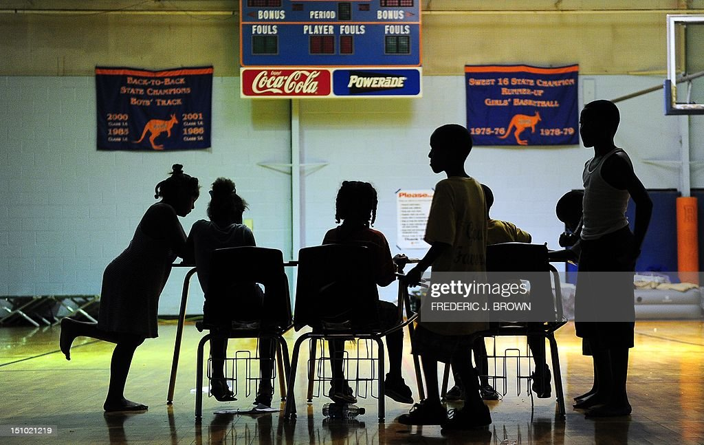 Children try to do their homework at an evacuation shelter at a high school gymnasium in Kentwood, northeast of New Orleans on August 30, 2012 in Louisiana, where Tropical Storm Isaac has dumped more rain onto an already saturated Gulf Coast leaving residents to seek safety from flooding. Authorities in two states along the US Gulf Coast urged residents to seek shelter amid fears the Percy Quin dam in Mississippi near the Louisiana border showed signs of damage due to the storm. AFP PHOTO / Frederic J. BROWN