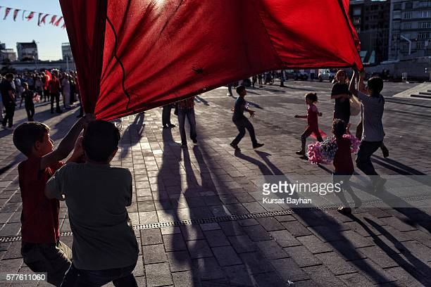 Children try to pull down the giant Turkish flag at Istanbul's central Taksim Square on July 19 2016 in Istanbul Turkey Clean up operations are...