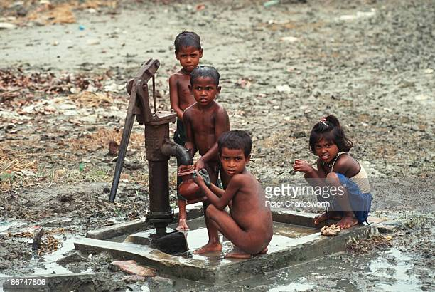 Children try to pump water from one of the few remaining artesian wells that has not been destroyed by saltwater brought in by one of the biggest...