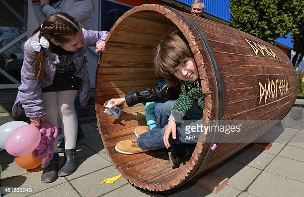 Children try to taste Diogenes' life in a barrel in the southern Russian city of Stavropol on April 1 2014 The sign on the barrel reads Diogenes'...