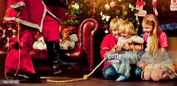 children trying to catch santa claus - naughty santa stock photos and pictures