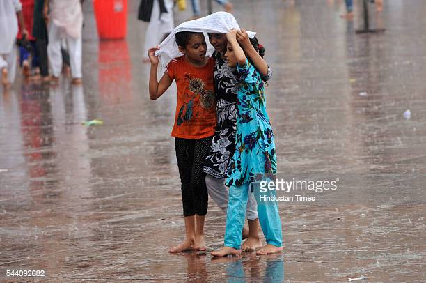 Children trying to shield themselves from rains near Jama Masjid on July 1 2016 in New Delhi India The capital received its first Monsoon rains...