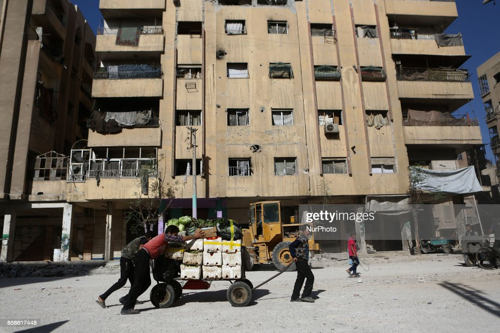 Children trying transport a wagon loaded with vegetables amid the destruction house after airstrikes on rebel. held Douma Outskirts of Damascus, Syria, 7 October 2017. At least 4 people got killed and more than 50 people got injured from airstrikes on the rebel.