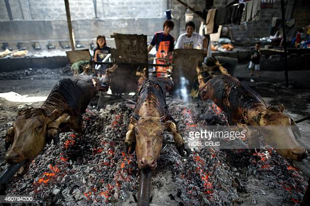 Children turn the skewers while roasting calves in Manila on December 23 for the busy holiday season Lechon or roasted calf has always been a regular...