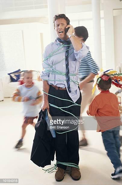 children (4-7) tying up father with phone cord (blurred motion) - mann gefesselt stock-fotos und bilder