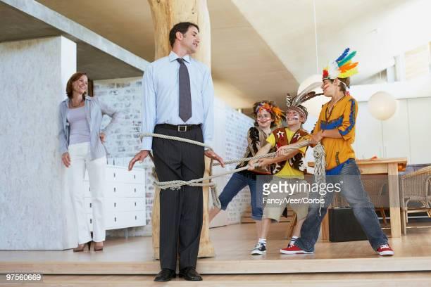 children tying up father with rope - junge gefesselt stock-fotos und bilder