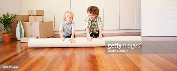 Children unrolling carpet in new house