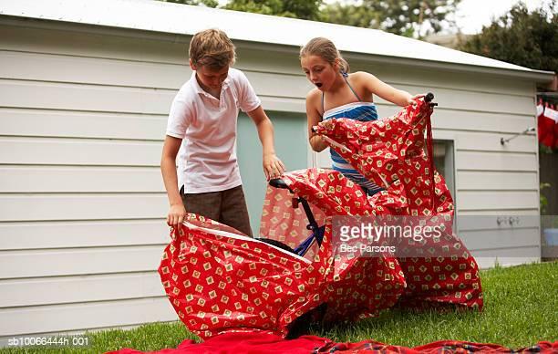 Kinder (9-12 Jahre) unwrapping Fahrrad von Einwickelpapier in yard