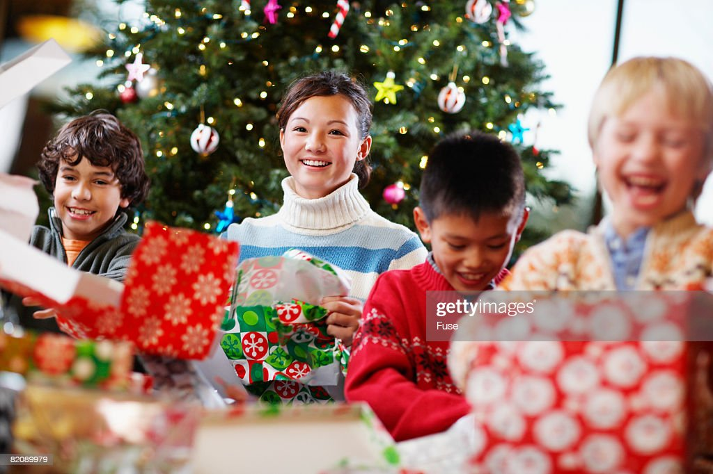Kids unwrapping christmas gifts