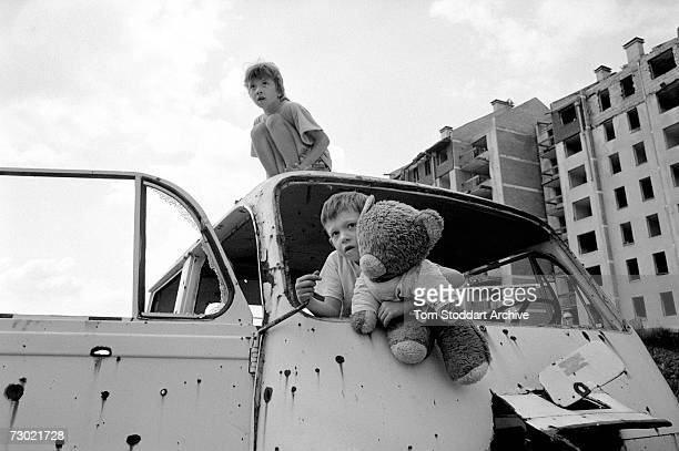 Children use a bullet riddled car as a playground near destroyed apartments in a heavily shelled frontline area of Sarajevo During the 47 months...