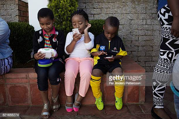 Children use mobile phones while their mothers attend a market selling famous brand clothes on April 27, 2013 in Soweto, South Africa. The monthly...
