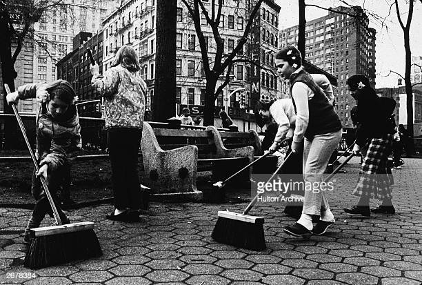 Children use push brooms to sweep a city park during Earth Day New York City 1970s