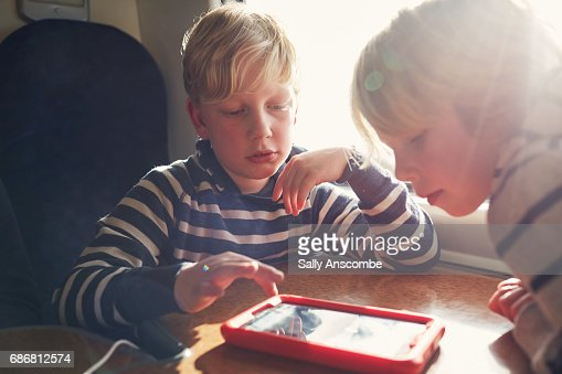 Children using a digital tablet on a train