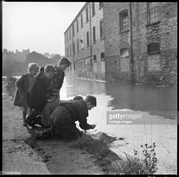 Children using a goldfish bowl to fish in the Caldon Canal, Hanley, Stoke-on-Trent, 1965-1968. Howson's Eastwood Sanitary Ware Works on Clifford...