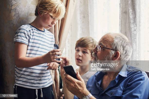 Children using a smartphone with their Grandfather