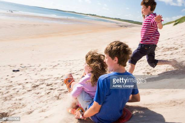 Children using body boards to slide down the sand dunes at Beadnell Bay, in Northumberland, UK.
