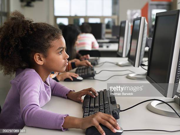 Children (6-8) using computers (focus on girl in foreground)