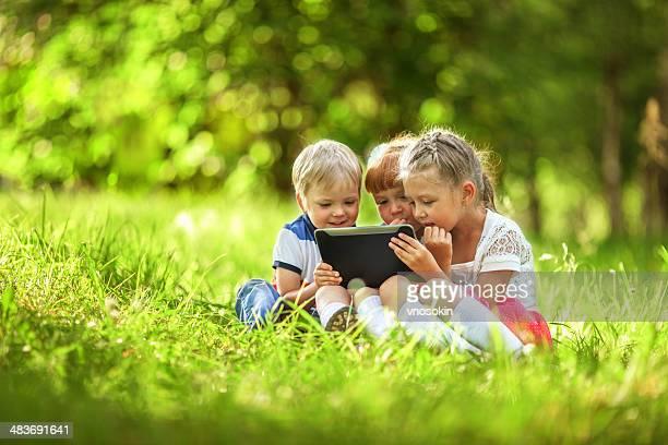 Kinder, die mit digitalen tablet im park