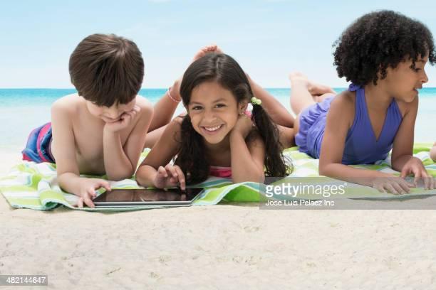 Children using digital tablet on blanket at beach