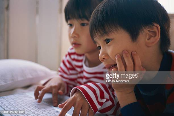 Children (4-7) using laptop on bed