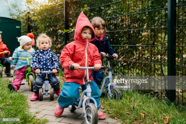 children using scooters in garden of a kindergarten - kindergarten stock-fotos und bilder