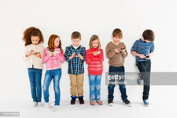 children using smartphones, standing in a row - child facebook stock photos and pictures