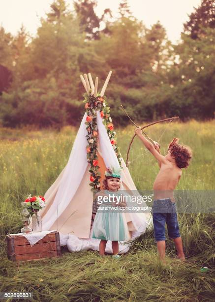 Children using their imagination outside teepee