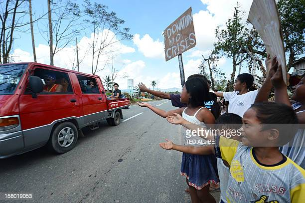 Children victims of devastating Typhoon Bopha beg for alms along a roadside in the town of Osmena in Compostela Valley province on December 9 2012...