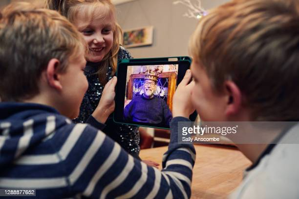 children video calling a relative at christmas - sally anscombe stock pictures, royalty-free photos & images