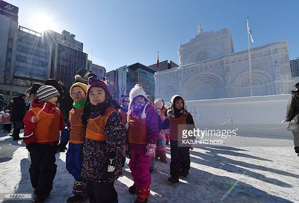 Children visit a large snow sculpture called the Manila Cathedral of Philippines during the 66th annual Sapporo Snow Festival on February 5, 2015....