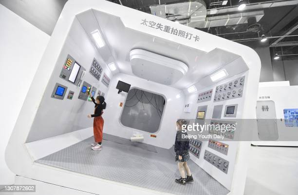 Children visit an interactive technological exhibition on the development of China's manned space program at China Science and Technology Museum on...