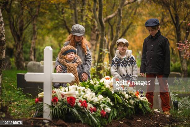children visiting grave of deceased loved one. - cemetery stock pictures, royalty-free photos & images