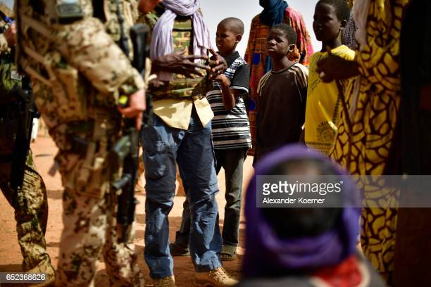 Children wach soldiers of the Bundeswehr the German Armed Forces while visiting a weekly cattle market on the outskirts of Gao on March 7 2017 in Gao...