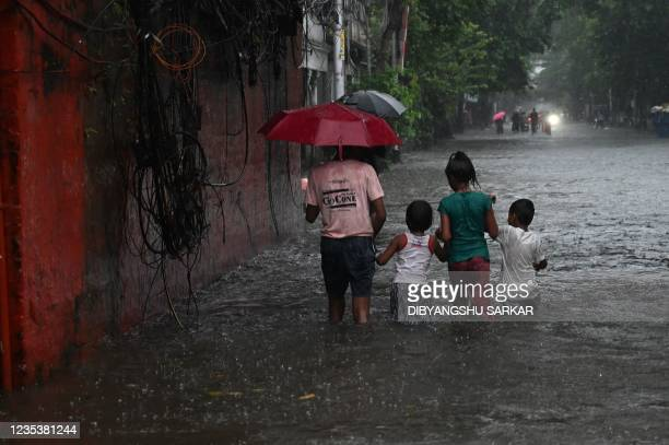 Children wade through a waterlogged street after heavy rainfall in Kolkata on September 20, 2021 reportedly triggered by cyclonic circulation formed...
