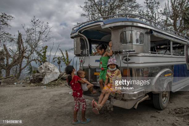 Children wait along a highway for relief goods on January 19 2020 in the village of San Guillermo Talisay Batangas province Philippines The...
