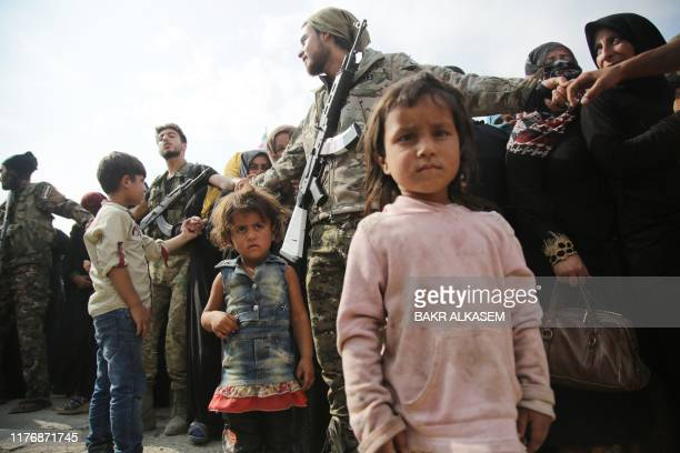 Children wait as members of Turkey-backed forces form a cordon to control a crowd of displaced Syrians gathering to receive aid provided by the...
