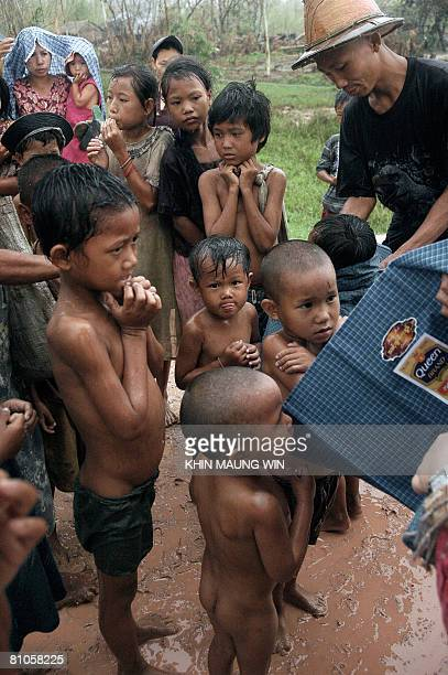 Children wait for relief food to be distributed to survivors of the cyclone Nargis in Kyaiklat in the Ayeyarwady Division of southwest Myanmar on 12...