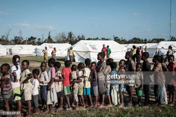 Children wait in a line to receive food distribution from a local supermarket at an evacuation center in Dondo about 35km north from Beira Mozambique...