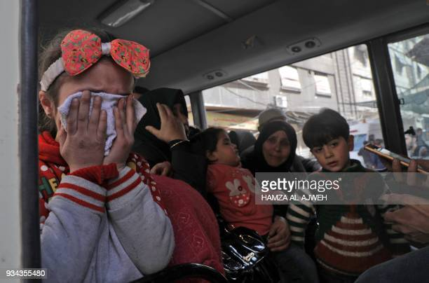 TOPSHOT Children wait to be evacuated from Douma Eastern Ghouta in Syrian Red Crescent buses on the eastern outskirts of the capital Damascus on...