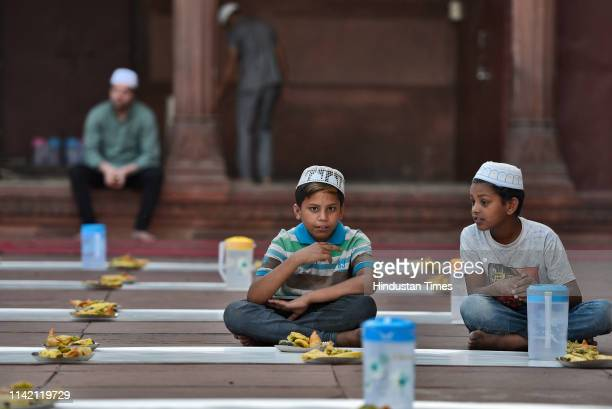 Children wait to break their fast on the first day of the holy fasting month of Ramadan at Jama Masjid on May 7 2019 in New Delhi India