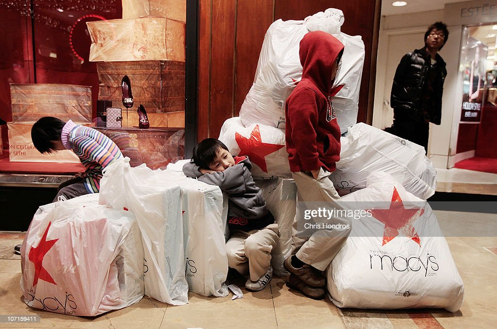Children wait with shopping bags inside Macy's department store on 'Black Friday' shopping day November 26, 2010 in New York City. Christmas shopping season is officially under way as Thanksgiving ends, and early signs point to a solid turnout for holiday shopping season.