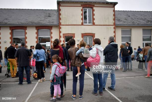 Children wait with their parents to enter a primary school on the first day of the new school year in Vertou western France on September 4 2017 / AFP...