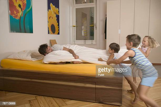 Children waking up father in bed