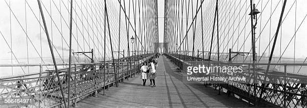 Children walk across the Brooklyn Bridge New York 1910
