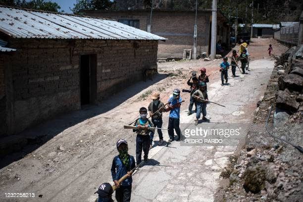 Children walk along a street as they prepare to take part in a training demonstration of the Regional Coordinator of Community Authorities vigilante...