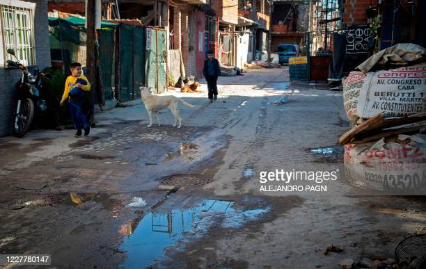 Children walk along an alley at the Padre Carlos Mugica neighborhood, also known as Villa 31 shantytown, in Buenos Aires, on July 25 amid a lockdown...