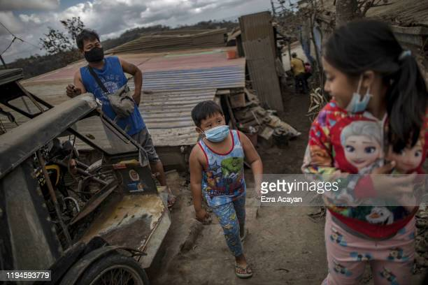 Children walk along an ash covered street on January 19 2020 in the outskirts of Tagaytay city Cavite province Philippines The Philippine Institute...